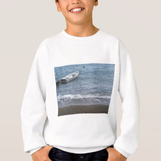 Single rowing boat moored in a harbor on the sea sweatshirt