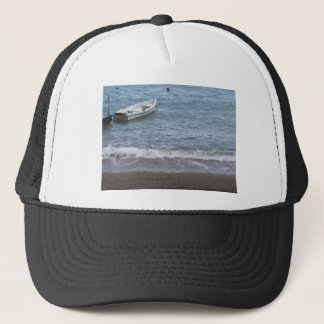 Single rowing boat moored in a harbor on the sea trucker hat
