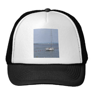 Single sailboat lies at anchor in a harbor cap