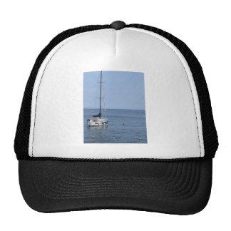 Single sailboat lies at anchor in a harbor cap