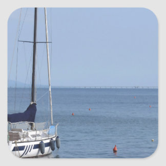 Single sailboat lies at anchor in a harbor square sticker