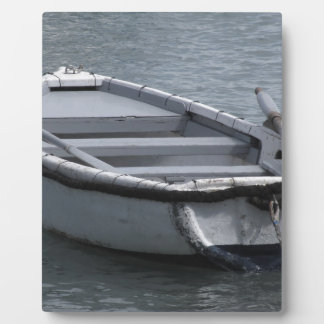Single wooden rowing boat on the sea plaque