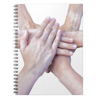 Six arms unite with hands on each other notebooks
