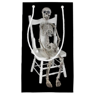 skeleton sitting on white chair small gift bag
