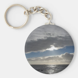 Sky with giants cumulonimbus clouds and sun rays key ring