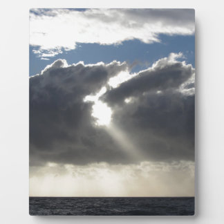 Sky with giants cumulonimbus clouds and sun rays plaque