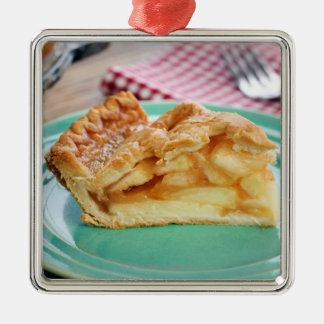 Slice of fresh baked apple pie on plate metal ornament