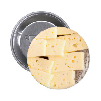 Slices dry hard yellow cheese on a plate closeup 6 cm round badge