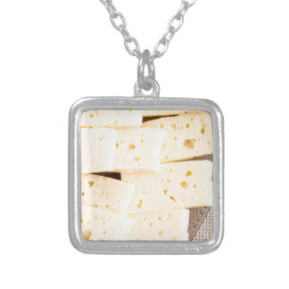 Slices dry hard yellow cheese on a plate closeup silver plated necklace