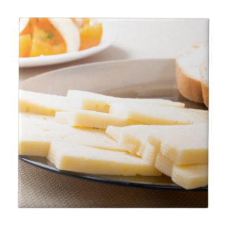 Slices of cheese and bread on a plate closeup small square tile