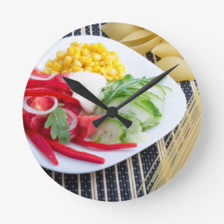 Slices of fresh raw vegetables round clock