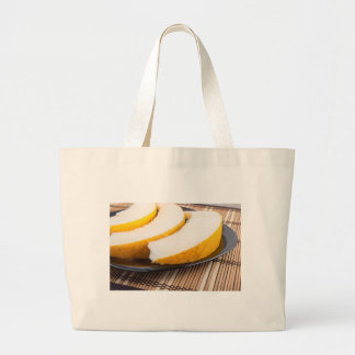 Slices of juicy yellow melon on a black plate large tote bag