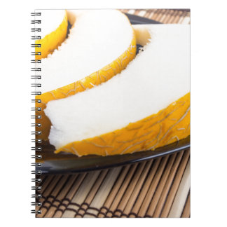Slices of juicy yellow melon on a black plate notebook