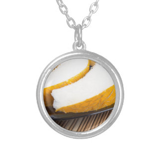 Slices of juicy yellow melon on a black plate silver plated necklace