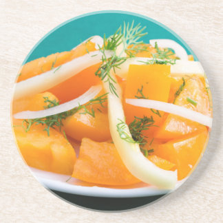 Slices of orange tomato on a plate with onions coaster