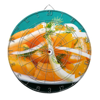 Slices of orange tomato on a plate with onions dartboard