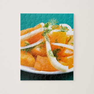 Slices of orange tomato on a plate with onions jigsaw puzzle