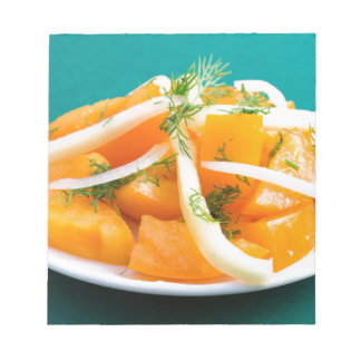 Slices of orange tomato on a plate with onions notepad