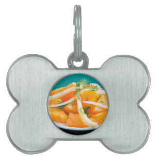 Slices of orange tomato on a plate with onions pet name tag