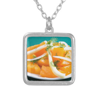 Slices of orange tomato on a plate with onions silver plated necklace