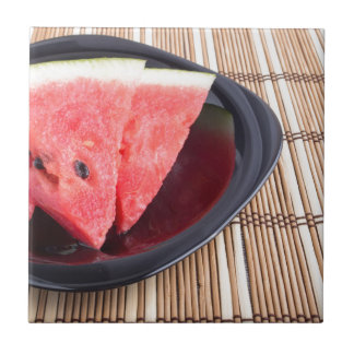 Slices of red watermelon on a black plate small square tile