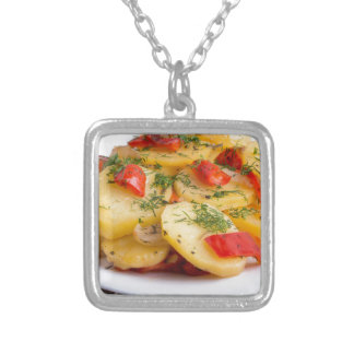 Slices of stewed potatoes and peppers on sackcloth silver plated necklace