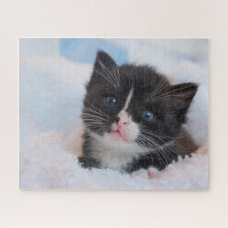 Small black kitten snuggling in the blankets jigsaw puzzle