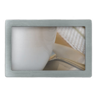 Small cup of espresso on a saucer with sugar belt buckle