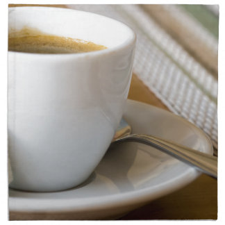 Small cup of espresso on a saucer with sugar napkin