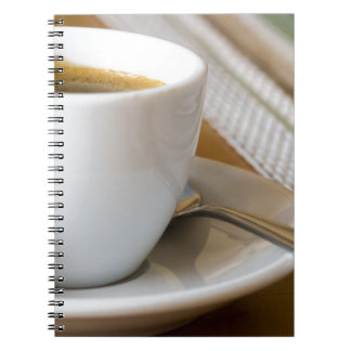 Small cup of espresso on a saucer with sugar notebooks