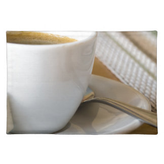 Small cup of espresso on a saucer with sugar placemat