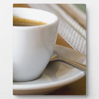 Small cup of espresso on a saucer with sugar plaque