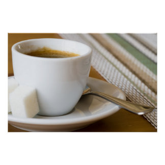 Small cup of espresso on a saucer with sugar poster