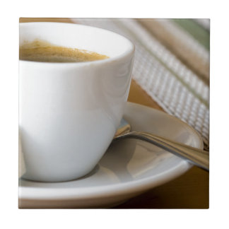 Small cup of espresso on a saucer with sugar tile