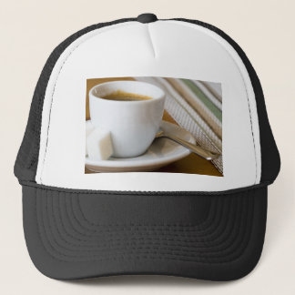 Small cup of espresso on a saucer with sugar trucker hat