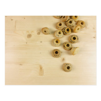 small donuts cascade on wood background postcard