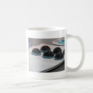 Small glazed chocolate cakes with hazelnut grains coffee mug