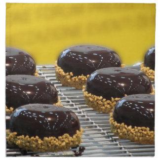 Small glazed chocolate cakes with hazelnut grains napkin