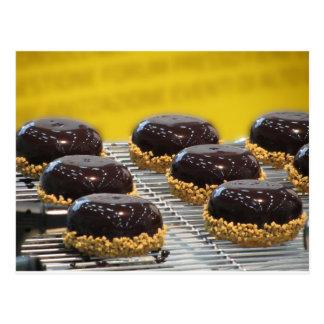 Small glazed chocolate cakes with hazelnut grains postcard