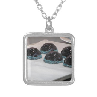 Small glazed chocolate cakes with hazelnut grains silver plated necklace