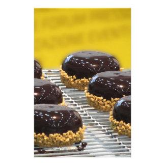 Small glazed chocolate cakes with hazelnut grains stationery