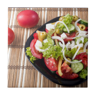 Small portion of vegetable salad of tomato small square tile