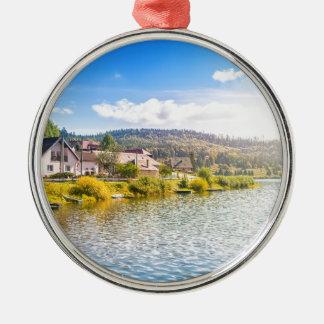 Small village near a lake metal ornament