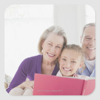 Smiling grandparents reading cookbook with square sticker
