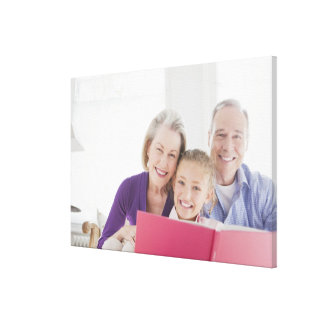 Smiling grandparents reading cookbook with stretched canvas print