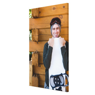 Smiling man posing with snowboard outside cabin canvas print