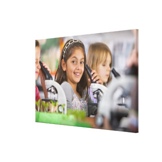 Smiling students peering into microscopes in gallery wrapped canvas