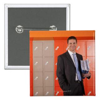 Smiling teacher holding paperwork near school 15 cm square badge