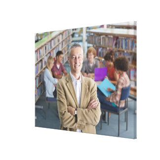 Smiling teacher standing in school library with canvas prints