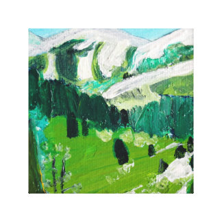Snow capped mountains in a green valley stretched canvas prints